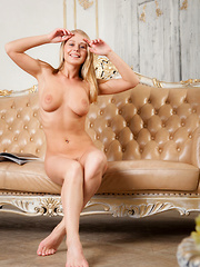 Sarika A shows off her big tits and trimmed pussy on the sofa.