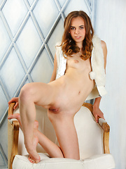 Gracie flaunts her petite body and sweet pussy on the chair.