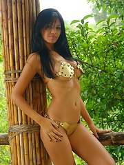 Karla Spice lets the sun caress her soft skin as she removes her golden laced up bikini