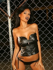 Karla Spice is dressed in a tiny leather outfit with a goth look