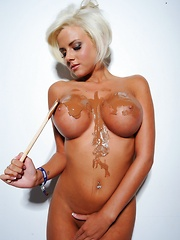 Hannah Elizabeth nude covering her breasts in chocolate